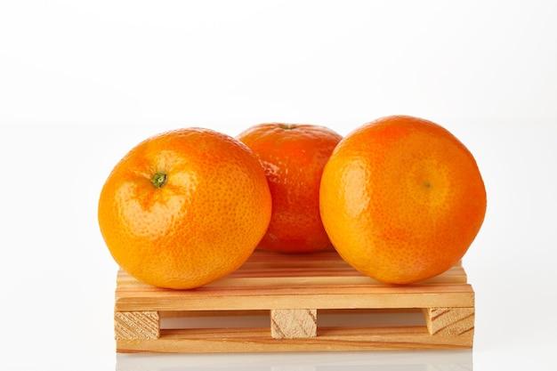 Tre mandarini sul pallet logistico in attesa di trasporto al luogo di destinazione isolato su sfondo bianco.