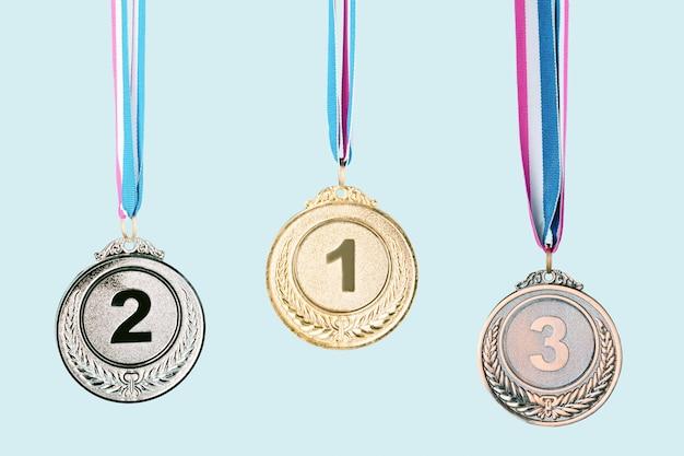 Tre medaglie (oro,argento,bronzo) su sfondo blu.concetto di premio e vittoria.spazio copia