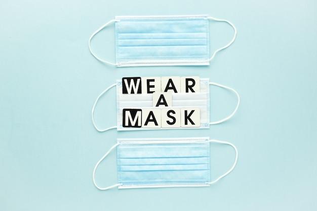 Tre maschere mediche e un messaggio di testo indossano una maschera su uno sfondo azzurro poster banner virus