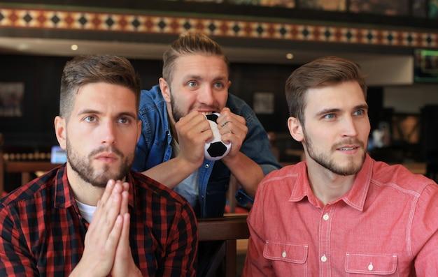Tre uomini in abiti casual fanno il tifo per il calcio e tengono in mano bottiglie di birra seduti al bancone del bar in un pub.