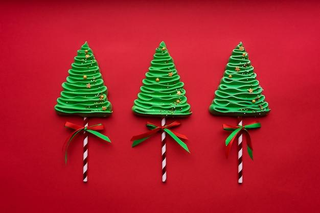 Tre alberi di meringa nello stile di capodanno su uno sfondo rosso.
