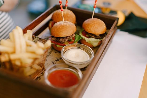 Tre mini hamburger su vassoio con due salse e patatine fritte Foto Premium