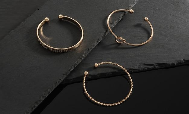 Tre bracciali dorati dal design moderno su lastre di pietra nera su sfondo nero