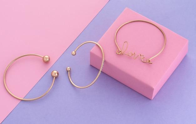 Tre moderni braccialetti d'oro su sfondo geometrico di colori pastello con spazio di copia