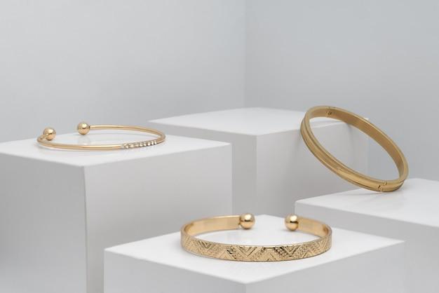 Tre moderni braccialetti dorati su scatole bianche con spazio di copia