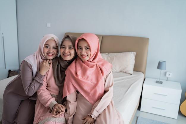 Una donna di tre musulmani che sorride quando esamina la macchina fotografica