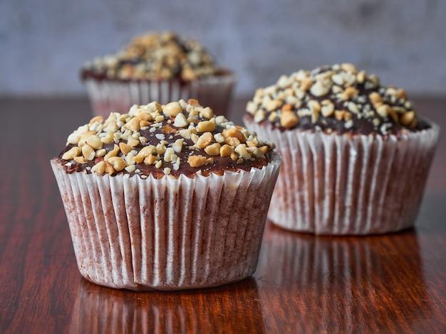 Tre muffin con arachidi e glassa al cioccolato in linea. messa a fuoco selettiva. avvicinamento.