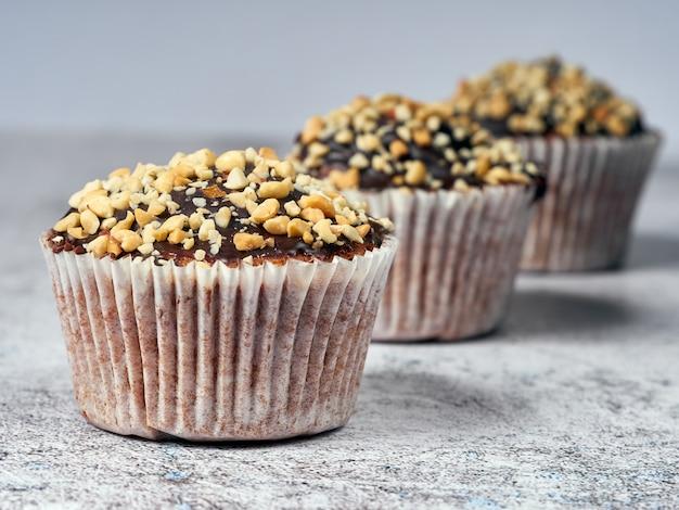 Tre muffin con arachidi e glassa al cioccolato in linea