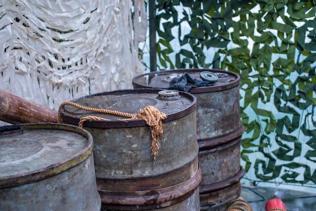 Tre vecchi barili di petrolio industriale un grande contenitore di ferro per carburante diesel o benzina su un sh...
