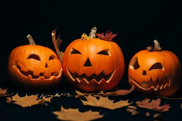 Tre zucca arancione con foglie di acero e ghiande per decorazioni per le vacanze autunnali di halloween