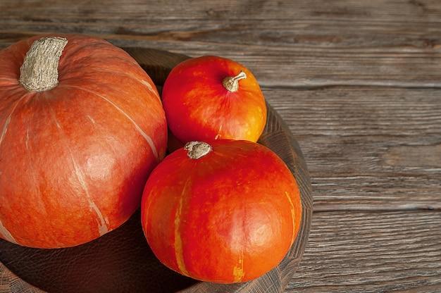 Tre zucche arancioni su un fondo di legno rustico