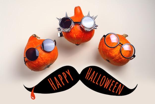 Tre zucche a bilanciere arancioni con occhiali e baffi su una luce