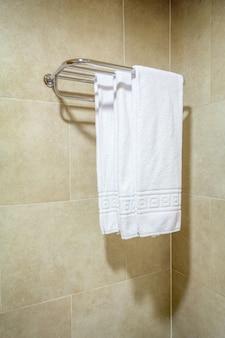 Tre asciugamani da bagno bianchi ordinati appesi su una rastrelliera