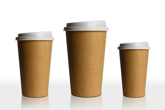 Tre bicchieri di carta di diverse dimensioni isolati su bianco