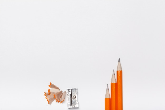 Tre matite, temperamatite e trucioli di legno isolati su sfondo bianco