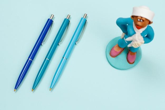 Tre penne e gesso figura di un dentista su sfondo blu. vista dall'alto.