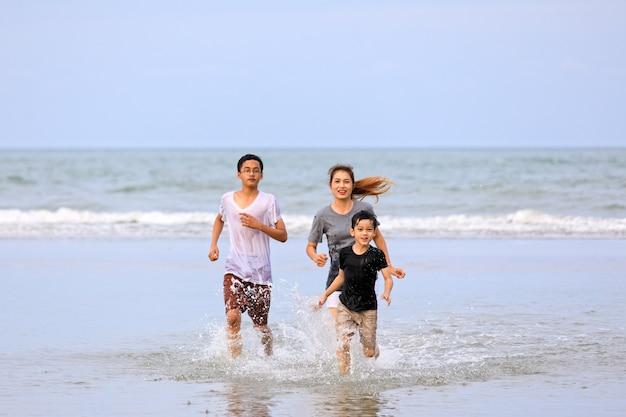 Una famiglia asiatica di tre persone che giocano a correre insieme sulla spiaggia tropicale con il cielo blu sullo sfondo