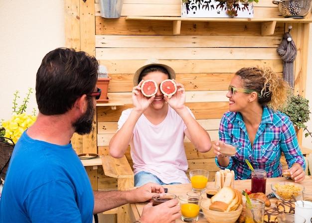 Tre persone a colazione con facce buffe. famiglia felice con figlio adolescente. sorrisi e amore. tavolo e sfondo in legno