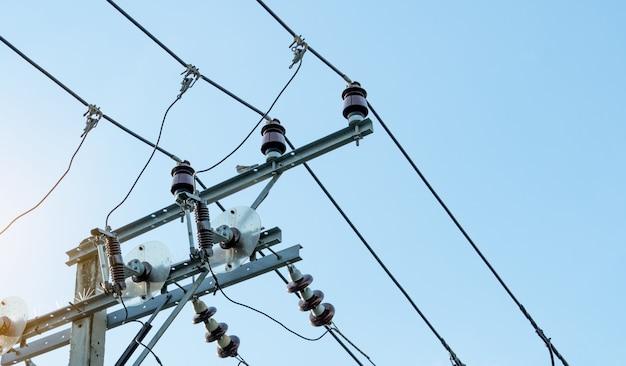 Energia elettrica trifase per il trasferimento di potenza dalle reti elettriche. energia elettrica per l'industria manifatturiera di supporto. poli elettrici ad alta tensione e linee di filo contro il cielo blu. potenza ed energia.