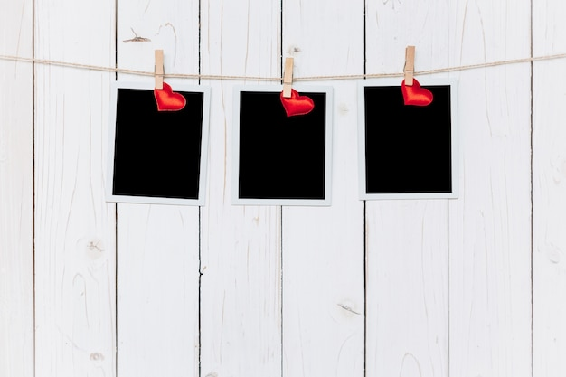 Tre fotogrammi in bianco e cuore rosso appeso su sfondo bianco di legno con spazio
