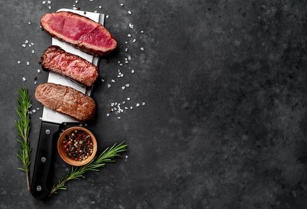 Tre pezzi di carne grigliati su un coltello da carne tre tipi di carne fritta, rara, media, ben cotta, con spezie