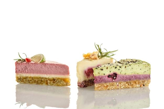 Tre pezzi di torta di cibo crudo su uno sfondo bianco.