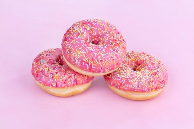 Tre ciambelle rosa con piccole caramelle su uno sfondo rosa