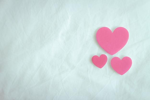 Tre cuori rosa sul foglio bianco assomigliano all'amore e alla famiglia in san valentino.