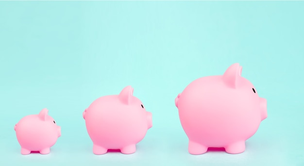Tre salvadanaio rosa su sfondo blu. concetto di crescita finanziaria.