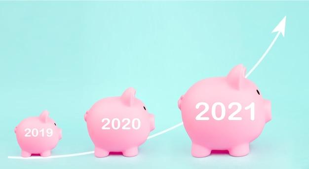 Tre salvadanaio rosa con freccia bianca ologramma digitale e segno anno 2021 su sfondo blu. crescita degli investimenti. risparmio finanziario ed economia bancaria
