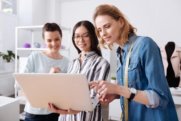 Tre piacevoli donne contente che leggono un feedback sul loro lavoro e sorridono con una di loro che tiene un laptop e l'altra che indica qualcosa con il dito