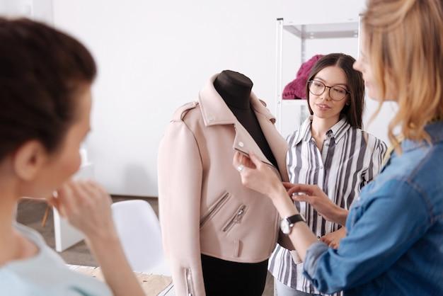 Tre piacevoli giovani donne in piedi intorno a un manichino con un'elegante giacca rosa appesa sopra.
