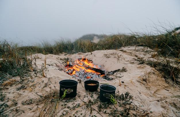 Tre pentole con cibo sulla sabbia con il fuoco