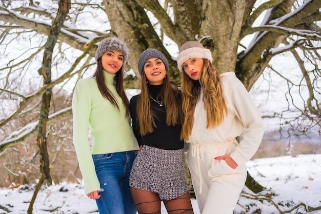 Tre amici piuttosto caucasici che si godono la neve in inverno sotto un albero, vacanze invernali sulla neve