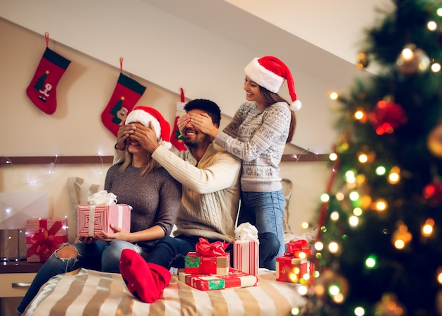 Tre amici piuttosto giocosi con il cappello di babbo natale seduti sul letto per le vacanze di natale e fanno un treno con gli occhi chiusi per un regalo a sorpresa.