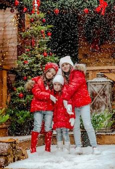 Tre belle ragazze in abiti invernali rossi e bianchi in posa nel cortile sul retro con nevicate e decorazioni natalizie.