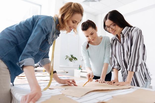 Tre belle giovani donne in piedi intorno al tavolo dell'atelier e discutendo insieme uno schema mentre una di loro lo indicava con una matita.