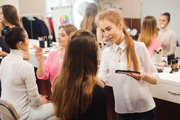 Tre truccatori professionisti lavorano con belle giovani donne. scuola di trucco professionale.