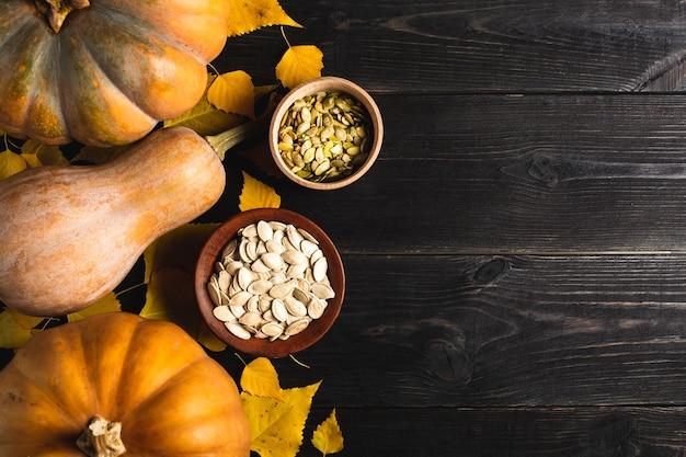 Tre zucche di diverse dimensioni su uno sfondo di legno nero con foglie gialle. piatto in ceramica e ciotola in legno con semi di zucca. situato su un lato. copia spazio. vista dall'alto.