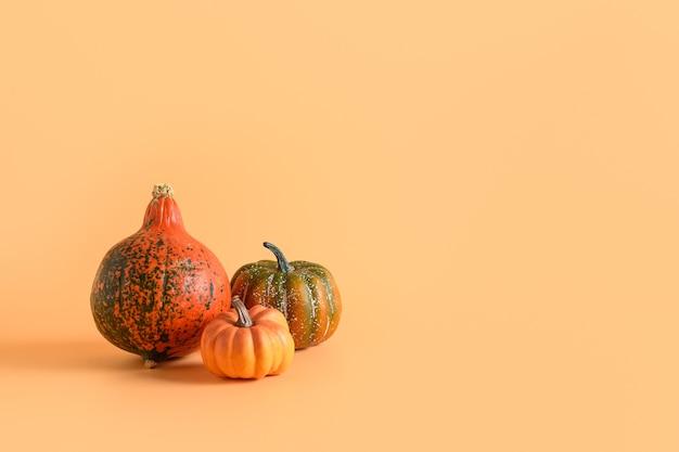 Tre zucche su sfondo arancione. giorno del ringraziamento o halloween mock up. copia spazio.