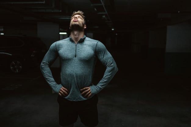 Tre quarti di bel sportivo caucasico in abbigliamento sportivo che tiene le mani sui fianchi e che riposa dopo l'esercizio. interno garage sotterraneo.