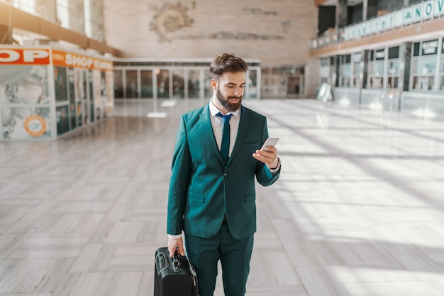 Una lunghezza di tre quarti dell'uomo d'affari barbuto sorridente nei bagagli della tenuta di usura convenzionale e nello smart phone mentre stando all'aeroporto. concetto di viaggio d'affari.