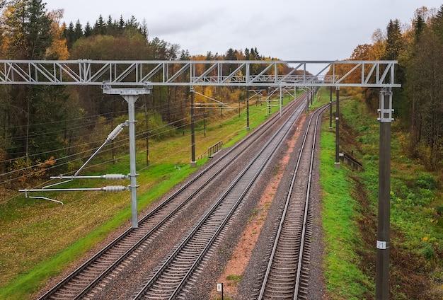 Tre binari ferroviari in autunno. nella cornice traversine, macerie, sassi, pali, aranci