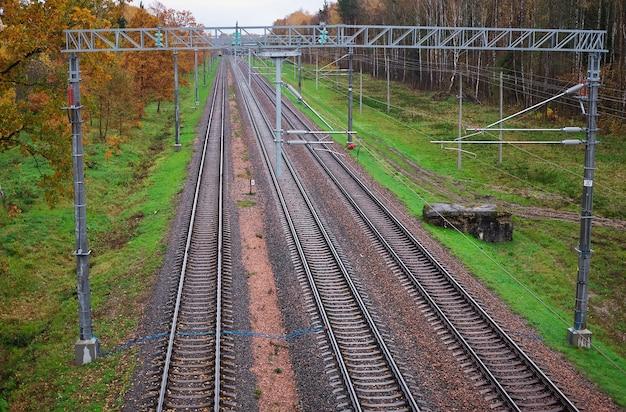 Tre binari ferroviari in autunno. nella cornice traversine, macerie, sassi, pali, alberi gialli e aranci