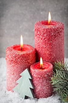 Tre candele rosse sulla superficie grigia, decorazioni natalizie. atmosfera d'avvento.