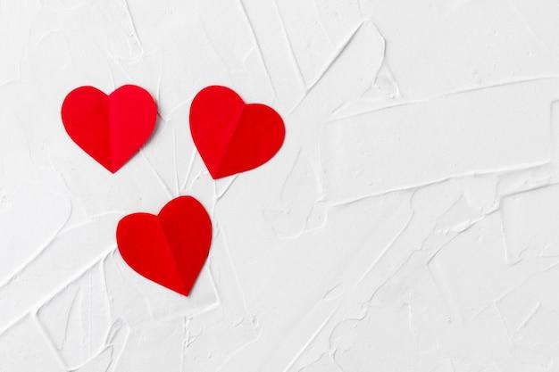 Tre cuori rossi del papper sulla struttura bianca del mastice. san valentino