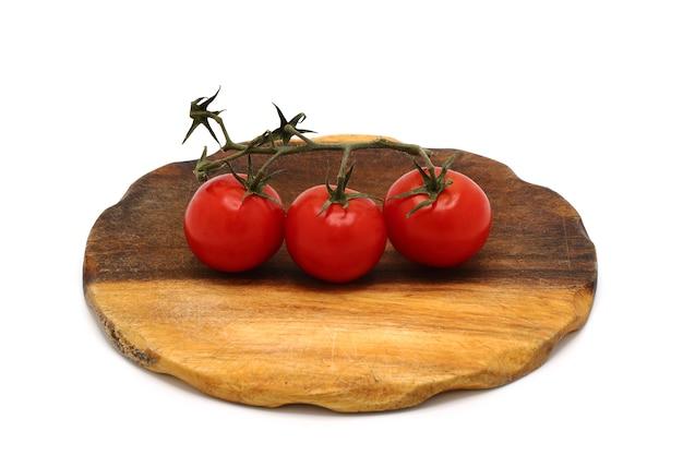 Tre pomodori rossi maturi su un tagliere su sfondo chiaro. prodotto naturale. colore naturale. avvicinamento.