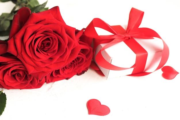 Tre rose rosse e una confezione regalo con un fiocco su un tavolo bianco e cuori rossi.