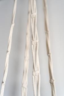 Tre nastri tessuti con la tecnica del macramè dal primo piano di fili di cotone naturale bianco.