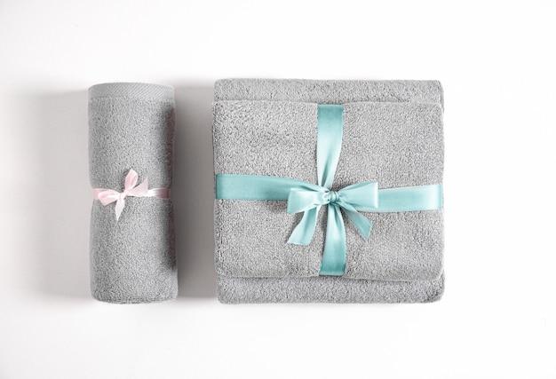 Tre asciugamani di spugna arrotolati e piegati legati da nastro rosa e blu isolato. pila di asciugamani di spugna blu e grigi contro uno sfondo bianco. vista dall'alto.